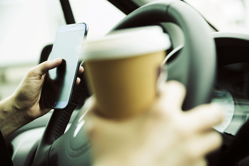 Driving with coffee and a phone is a distraction that could kill.